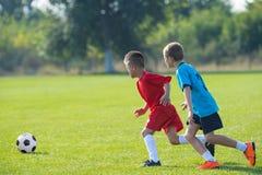 Boys kicking ball. Boys kicking football on the sports field royalty free stock photos