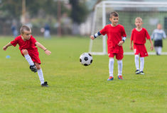 Boys kicking ball. Boys kicking football on the sports field Stock Images