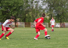 Boys kicking football Stock Images
