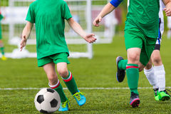 Boys Kicking Football on the Sports Field. Young boys playing football soccer game. Running players in blue and yellow uniform. Final game of football tournament Royalty Free Stock Image