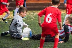 Boys kicking soccer ball at sports field. Boys kicking football on the sports field royalty free stock photo