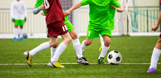 Boys Kicking Soccer Football Game. Running Young Soccer Players Stock Photo