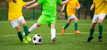 Boys Kicking Soccer Football Game. Running Young Soccer Players Royalty Free Stock Photos