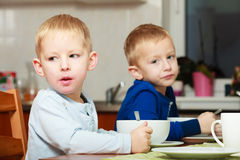 Boys kids children eating corn flakes breakfast meal at the table Royalty Free Stock Photos