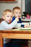 Boys kids children eating corn flakes breakfast meal at the table Stock Images