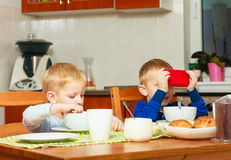 Boys kids children eating corn flakes playing with mobile phone Stock Photography