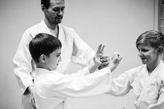 Boys in a kimono have an aikido training with a coach. royalty free stock photo