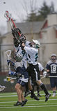 Boys Lacrosse climbing for the ball Royalty Free Stock Photo