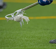 Boys Lacrosse Ground ball. Boy's Lacrosse player bending down to scoop up a ball during a game on a Turf field royalty free stock photos