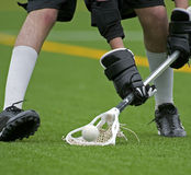 Boys Lacrosse scooping up the ball. Boys Lacrosse players bending down to scoop up a ball durring a game on a turf field royalty free stock photography