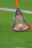 Boys Lacrosse stick. Colorful Boys lacrosse player scooping up a loose ball Royalty Free Stock Photography