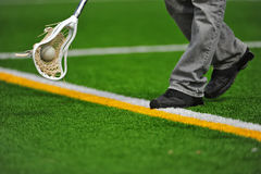 Boys lacrosse stick and ball. High school boys varsity lacrosse stick head catching a ball on a turf field as it goes out of bounds Stock Photography