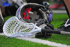 Boys lacrosse stick and helmet. High school boys varsity lacrosse stick head laying on a turf field with a glove and helmet in the background Royalty Free Stock Images
