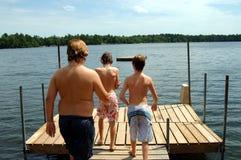 Boys at lake. Three boys walking on a dock at summer camp Stock Photos