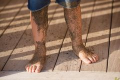 Boys legs covered with sea sand. Boy is standing in jeans on wooden floor his legs covered with sea sand Stock Image