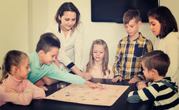 Boys and little girls playing at board game. Cheerful glad boys and little happy girls playing at board game indoors Royalty Free Stock Photo
