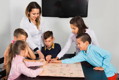 Boys and little girls playing at board game Stock Photography