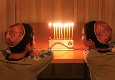 Boys Look at Hanukkah Menorah. Two jewish boys wearing kipahs look at a hanukkah menorah with candles