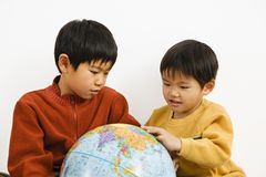 Boys looking at globe. Two Asian boys looking and pointing at world globe Stock Image