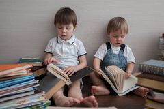 The boys are looking at open books. royalty free stock photo