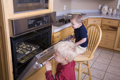 Boys looking in oven Royalty Free Stock Photos