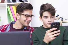 Boys looking at screen of mobile phone. Two boys, with amused expressions, looking at the screen of a mobile phone, office or study background royalty free stock image
