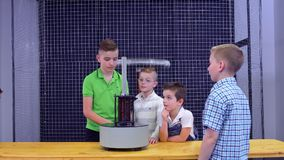 Boys makes experiment with electromagnetic fountain and metal ring. Children have an experiment with electromagnetic fountain. The boys put metal ring on the stock video footage