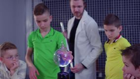Boys makes experiment with Tesla coil and glass sphere. Children and laboratory assistant make physical experiment with Tesla coil in scinetific museum. Boys stock footage