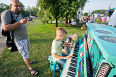 Boys making music & playing piano on a green playground Stock Photography