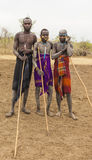 Boys and a man from Mursi tribe with spears in Mirobey village. Stock Photography
