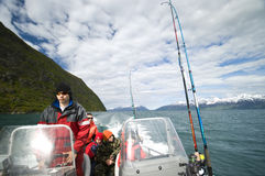 Boys in motorboat. A young boy driving or piloting a small motorboat on a day of fishing stock photography