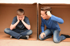 Boys in moving box. Friends in conflict sitting in an empty moving box royalty free stock image