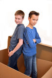 Boys in moving box. Boys standing in an empty moving box royalty free stock images