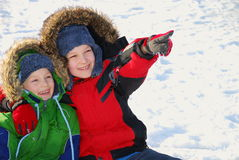 Boys outside in winter snow. A view of two boys outside in the winter snow as one points to something for his brother to see Stock Photo