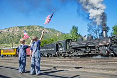 Boys in overalls wave American flag train departure Stock Image