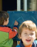 Boys painting on a blackboard. One out of focus Stock Images