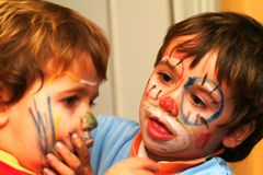 Boys painting his faces. Two boys painting his faces Stock Photo