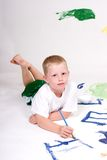 This boys is painting pictures. A boy is painting pictures on a large white sheet of paper Royalty Free Stock Photo