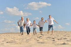 Boys with parents running on sand Royalty Free Stock Photography