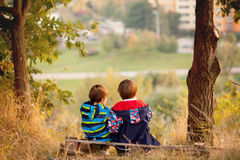 Boys in a park, sitting on a bench Stock Photo