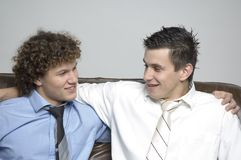Boys / partnership. Two boys in relaxed business attire sitting on a couch looking at each other Stock Photos