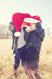 Children peeking under Christmas hat Royalty Free Stock Photography