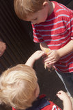 Boys petting baby chick. Two boys pet a baby chick at a farm Royalty Free Stock Photo