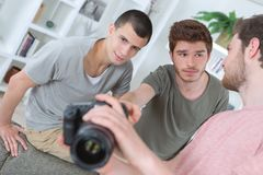 Boys with photo camera taking pictures indoors Royalty Free Stock Images