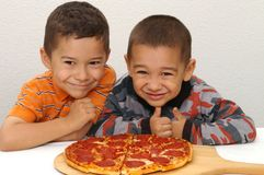 Boys and Pizza. Two young brothers ready to eat a pepperoni pizza stock photos