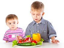 Boys and the plate of vegetables Royalty Free Stock Photos
