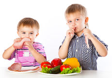 Boys and plates of vegetables and meat Royalty Free Stock Image