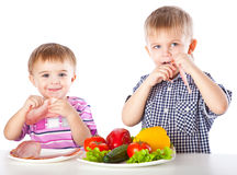 Boys and plates of vegetables and meat Royalty Free Stock Photo