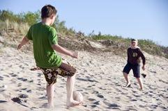 Boys play Beach football. Two boys playing football on a beach royalty free stock image