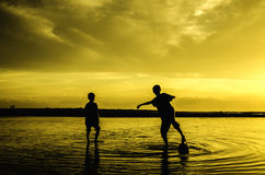 Boys play beach soccer during sunset sunrise Stock Photo